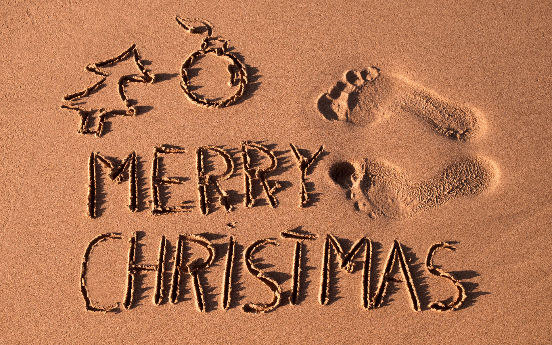 Merry Christmas written on Sand
