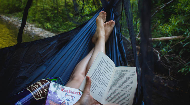 sitting in a hammock reading